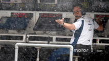 A Williams team member checks the rain fall from the pit wall