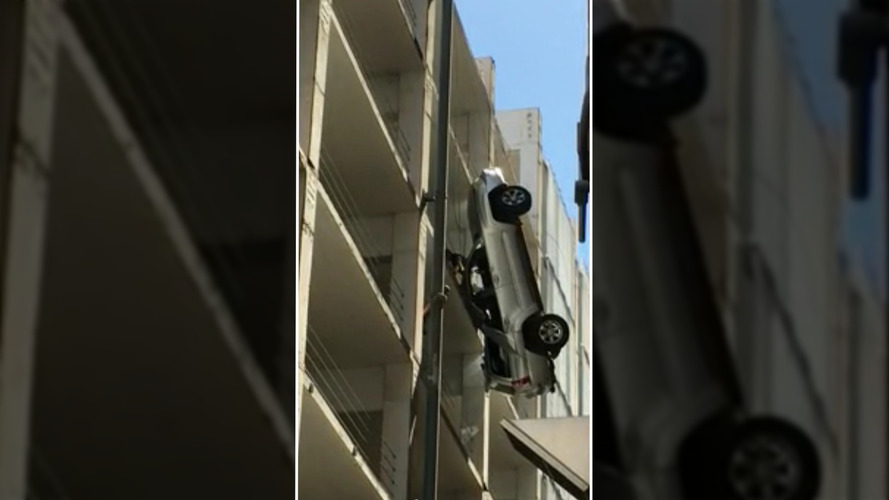 SUV precariously dangles off the side of a building, driver escapes
