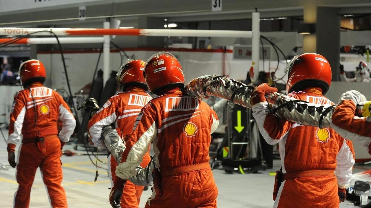 Ferrari pit crew carrying fuel hose