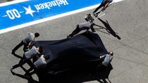 Mecânicos empurram o McLaren MCL32 de Fernando Alonso
